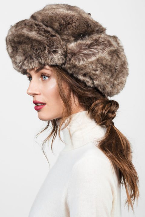A pretty knotted ponytail with soft, face-framing pieces does the trick of adding femininity to a heavy hunting hat. Separate your hair into three sections like you would for a classic braid, then tie the two on the outside together in a knot in front of the middle section. Wrap them around and knot them again in the back, and finish by securing the whole ponytail with an elastic. Albertus Swanepoel Bambi hat, $250, albertusswanepoel.com; White + Warren Essential Cashmere Turtleneck, $198, whiteandwarren.com.