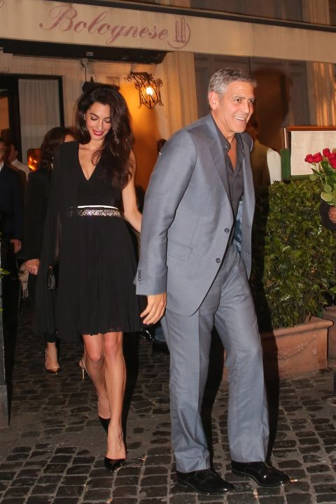 In a black Giambattista Valli pleated dress leaving a dinner date with George in Rome.