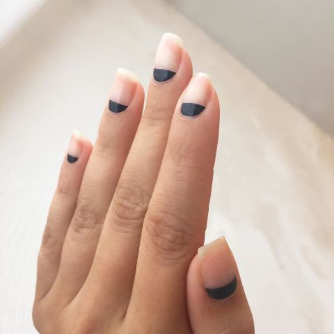 Try this easy negative design by painting matte black to the half moon of each nail.Design by @nataliepavloskinails