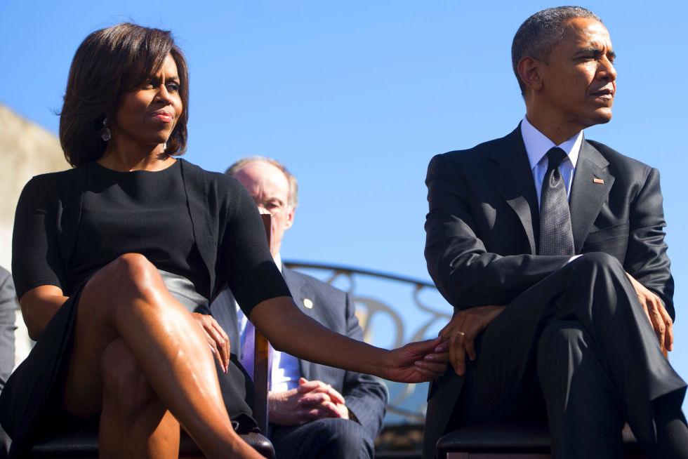 US President Barack Obama and First Lady Michelle Obama look on during an event marking the 50th Anniversary of the Selma to Montgomery civil rights marches at the Edmund Pettus Bridge in Selma, Alabama.  US President Barack Obama rallied a new generation of Americans to the spirit of the civil rights struggle, warning their march for freedom 'is not yet finished.' In a forceful speech in Selma, Alabama on the 50th anniversary of the brutal repression of a peaceful protest, America's first black president denounced new attempts to restrict voting rights.