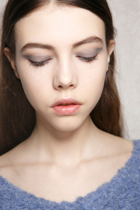 """The vibe:""""It's cool, but slightly rebellious and intellectual,"""" Pat McGrath said backstage. Get the look: McGrath created a """"pulled-out"""" eye shadow look by lining the eyes with beige and then creating a rectangular shape on the lids with gray. The rest of the face was brightenedwith highlighter on the bridge of the nose, cupid's bow, cheeks, and inner corners of the eyes. The kit: Victoria Beckham Estée Lauder Modern Mercury Highlighter, Eye Kajal Duo in Vanille. The gray shadow is an unannounced product coming soon."""