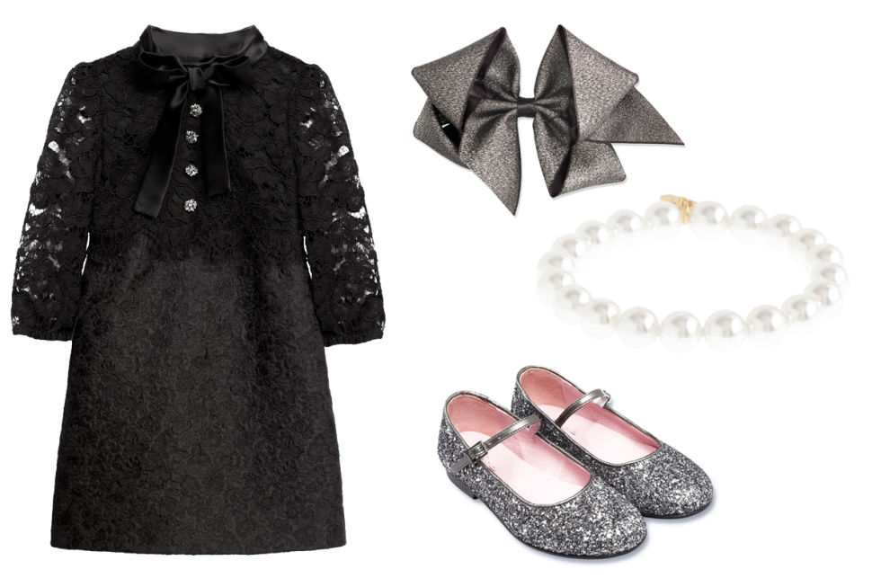 Dolce & Gabbana Lace and Brocade Dress With a Black Satin Collar, $908; melijoe.comJacadi Glitter Mary Janes, $102; jacadi.comMarie-Chantal Large Sparkle Hair Bow, $15; mariechantal.comJ.Crew Pearl Bracelet, $13; jcrew.com