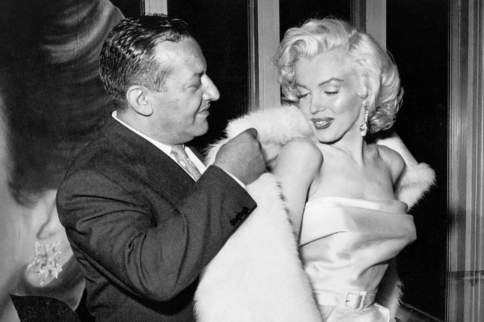Being helped into her coat by Ciro's restaurant owner Herman Hover in 1957.
